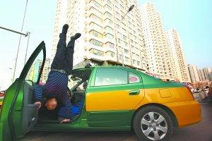 北京出租司机等活时手扶车门练倒立
